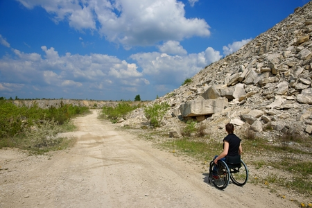 Disabled woman riding a wheelchair, path in a quarry Stock Photo