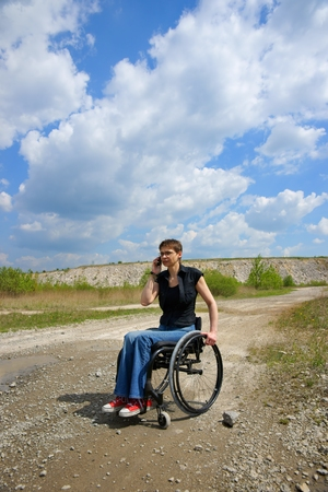 Disabled woman conversing on mobile phone outdoors, path in a quarry