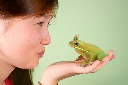 Teenage girl kissing Tree frog  Litoria infrafrenata  with a crown on his head photo