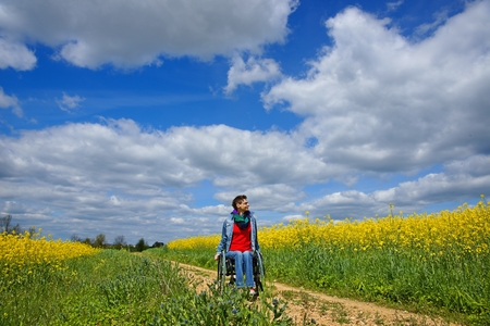 Disabled woman riding on a wheelchair between oilseed rape fields, spring