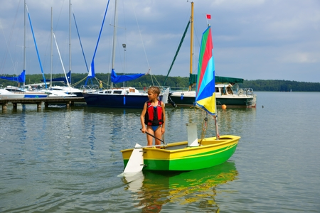 Sailing, Girl flows in a sailboat on the lake,  in the background marina for yachts