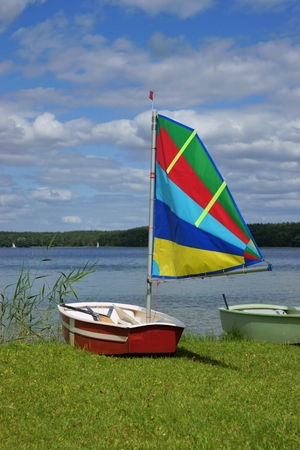 stretched out: Sailing, sailboat Optimist with colored sail, stretched out on the shore of the lake Stock Photo