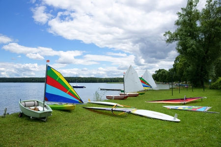 stretched out: Sailing, sailboats Optimist and Windsurfing Boards, stretched out on the shore of the lake Stock Photo