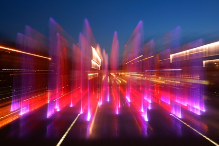 zooming: Fountain, zooming, colored illuminated flowing water by night, abstract as background