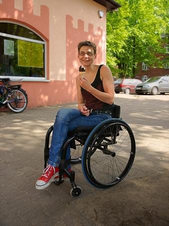 paraplegico: Mujer lisiada sonriendo y helado comido, escena urbana Foto de archivo