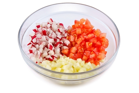 into: Tomatoes cucumbers and radishes cut into cubes in a glass bowl on a white background Stock Photo