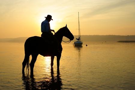silueta ciclista: Jinete en un caballo al amanecer Foto de archivo