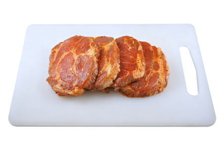 Meat, Pork neck in marinade and on a chopping boardon, on a white background