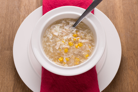 sweetcorn: chicken sweetcorn soup in a bowl with a spoon Stock Photo