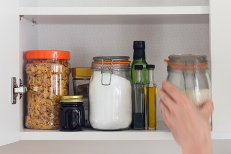 stocked kitchen pantry with food - jars and containers of cereals, jam, coffee, sugar, flour, oil, vinegar, rice Stockfoto