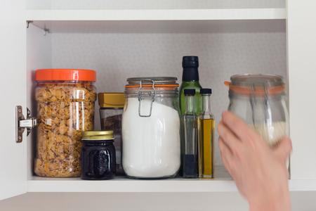 surtida despensa de la cocina con alimentos - frascos y envases de cereales, mermelada, café, azúcar, harina, aceite, vinagre de arroz,