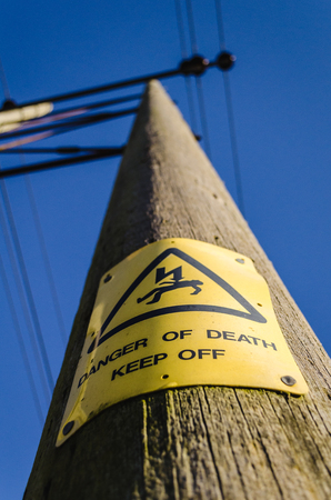or electrocution: warning yellow electrocution sign on electrical pole against blue sky Stock Photo