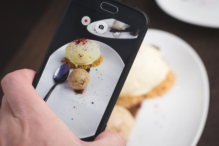 concep: Taking picture of food  with phone. Ice cream. Cellphone photography. Hand holding smartphone. Stock Photo
