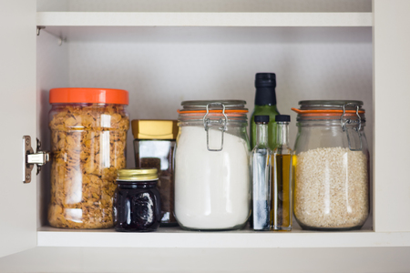 stocked kitchen pantry with food - jars and containers of cereals, jam, coffee, sugar, flour, oil, vinegar, rice Foto de archivo