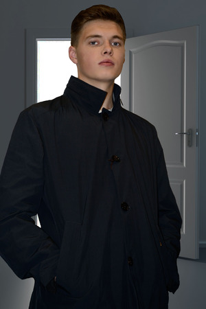 against the current: male model in coat against a door, brand-new coat, current men fashion