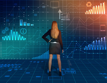 business woman standing and looking back at the charts photo