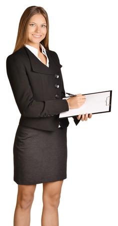 ビジネスの女性は、クリップボードにボールペンを書き込みます