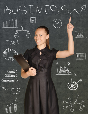 young woman legs up: Business woman holding a clip board and points to the chalk-drawn graphics. Stock Photo