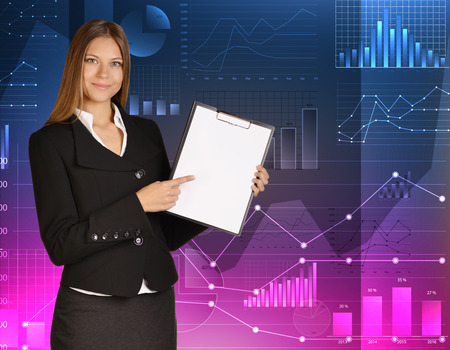 Business woman standing against background of financial charts and holding clipboard. photo