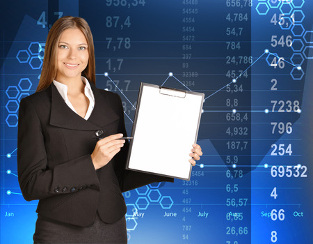 Business woman standing holding a clip board and ballpoint pen. photo