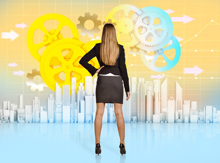 mechanical back: Business woman turned back looking at colorful office skyscrapers. Stock Photo
