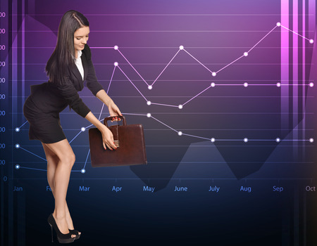 Business woman opens the briefcase standing on a background of diagrams. photo