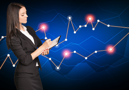 Business woman writing in a clip board on a background of financial charts. photo