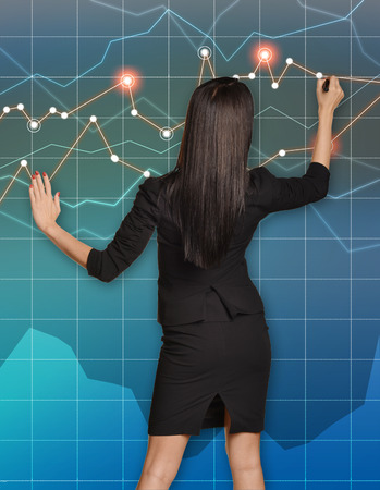 Business woman draws felt pen line graphs on the virtual wall. photo