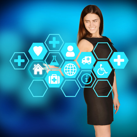 Business woman clicks on icon house located in hexagon background photo
