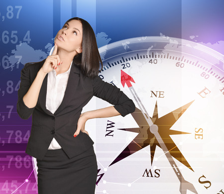 dial compass: Office girl holding a finger on his chin standing on the background of the compass Stock Photo
