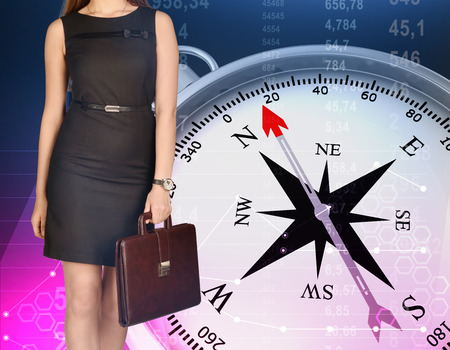wind rose: Girl holding leather briefcase in his hand standing on background of compass. Stock Photo