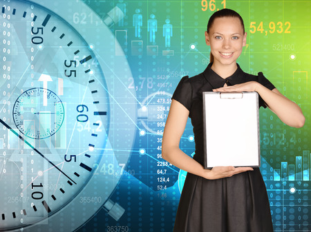 Young girl in a dress stands on background stopwatch holding clipboard. Stock Photo