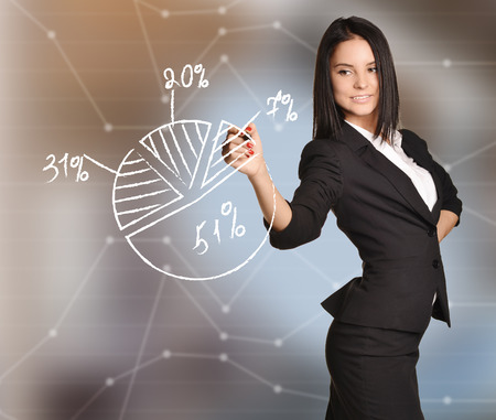 Girl draws pie chart percent standing on abstract background.