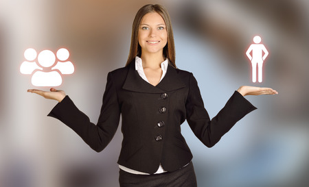 commands: Woman holds a human icons and commands people. Stock Photo