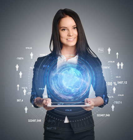 Young girl holding tablet in hands of a virtual digital globe and icons on sides. Stock Photo