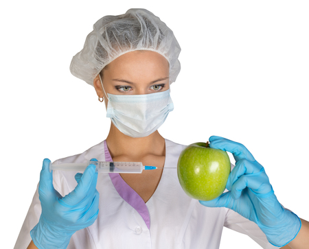 genetically modified: Woman holding an apple and is injected with a syringe. Genetically modified foods. Stock Photo