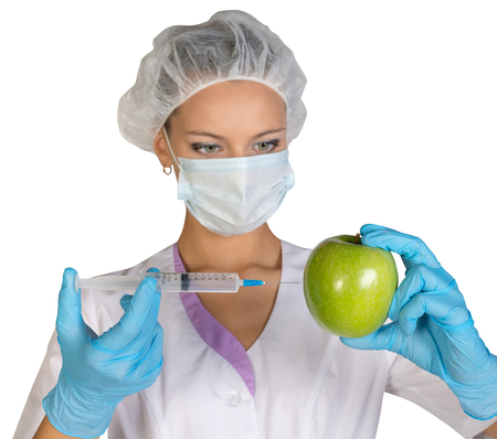 genetically modified: Woman holding an apple and is injected with a syringe. Genetically modified foods. Archivio Fotografico