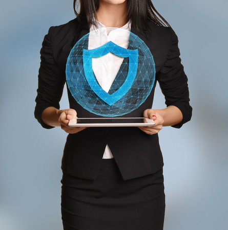 shield: Beautiful girl holding a tablet with digital network globe and shield icon.