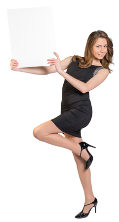 one sheet: Young girl is holding a big empty billboard, standing on one leg. Stock Photo