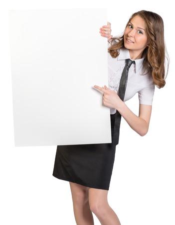 hoja en blanco: La mujer mira desde detrás de gran cartel en blanco que muestra el dedo índice sobre él.