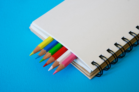 Notepad with colored pencils on a blue surface.