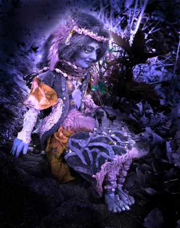 violett fairy doll figure sitting on stone in woodland.
