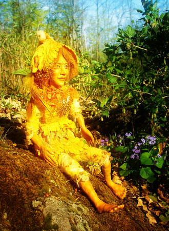 golden sunny fairy doll figure sitting on stone in woodland. Stock Photo