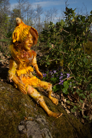 fairy doll handmade figure sitting on stone in woodland.