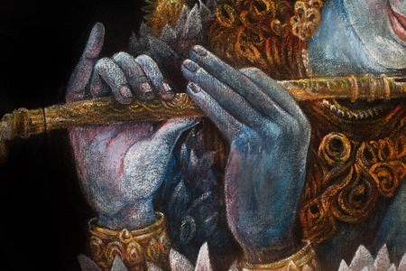 krishna: hands of lord krishna playing flute, detail with lotus pattern.