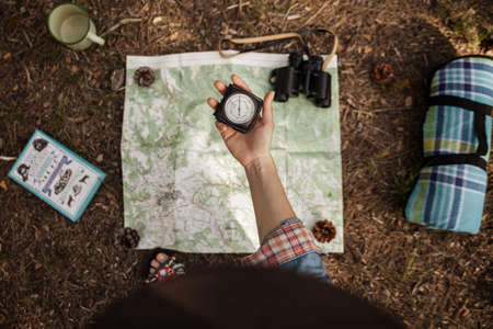 a girl is holding a compass to orientate in the forest with a map.