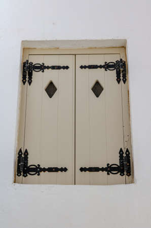 White shutters with diamond shaped windows