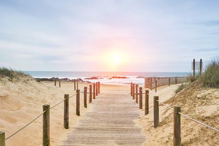 Camino de madera en la playa con vista al mar