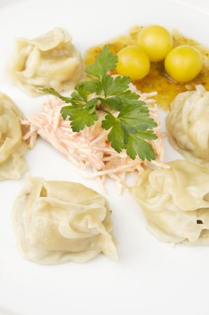 Fresh oriental dumplings made on steam and served on a white plate photo