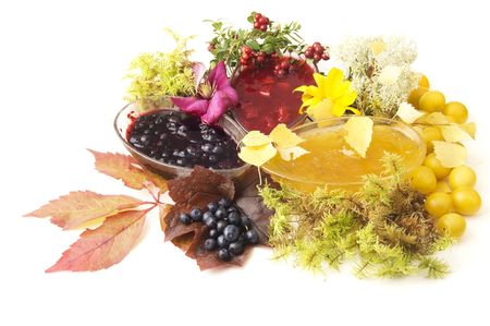 Jam of cowberries, cherry plum and bilberries and fresh fruits with flowers on white background Stock Photo